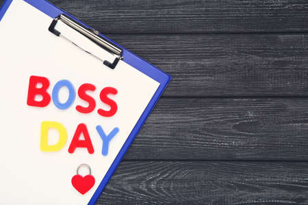 Colorful inscription Boss Day with clipboard and padlock in shape of heart on wooden black background