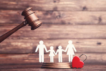 Family figures with red heart and gavel on brown wooden table Stock fotó