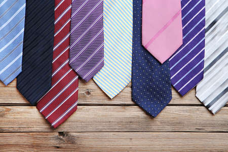 Colorful neckties on brown wooden table