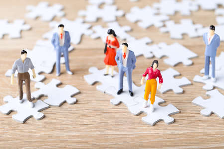 Miniature people with white jigsaw puzzles on wooden table