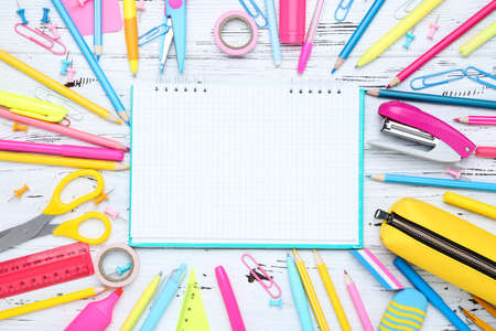 Different school supplies with blank sheet of paper on white wooden background