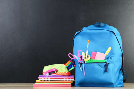 Backpack with school supplies on black background