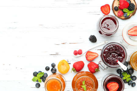Sweet jam in glass jars with ripe berries on white wooden table 스톡 콘텐츠