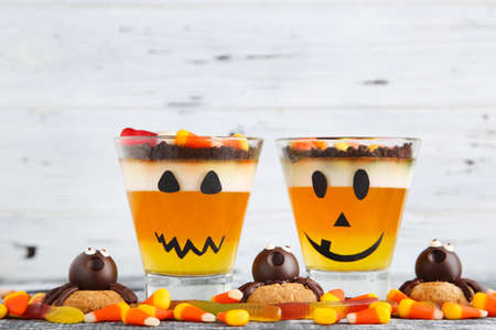 Halloween jelly in glasses with candies and cookies on wooden table