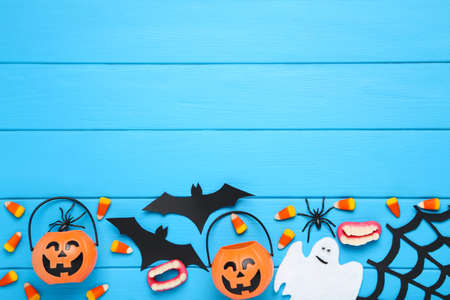 Halloween paper bats, ghost with candies and spiders on blue wooden background Фото со стока