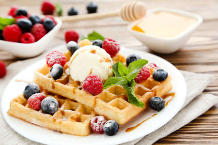 Tasty waffles with fresh berries and ice cream on brown wooden background