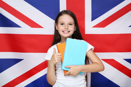 Young beautiful girl holding books and showing thumb up on british flag background