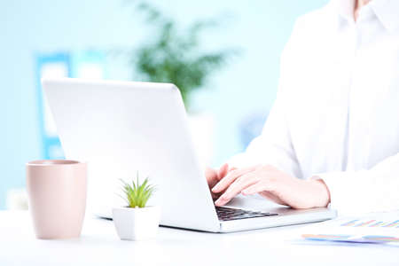 Office worker working on a laptop with cup of drink