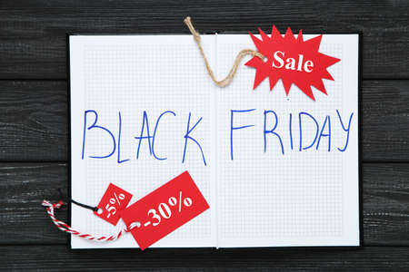 Inscription Black Friday in notepad and red tags on black wooden background Standard-Bild