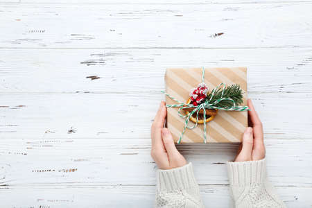 Female hands holding gift box on wooden background