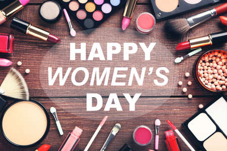 Different makeup cosmetics with text Happy Womens Day on brown wooden table
