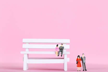 Miniature people with small wooden bench on pink background Banque d'images