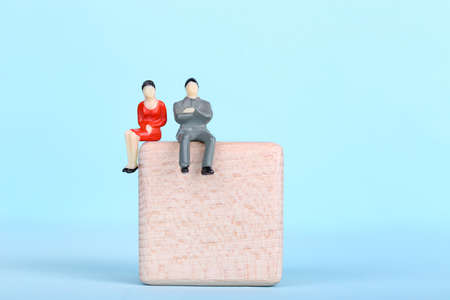 Miniature people with wooden cube on blue background