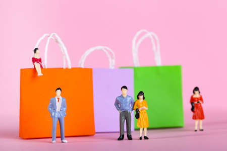 Miniature people with paper shopping bags on pink background