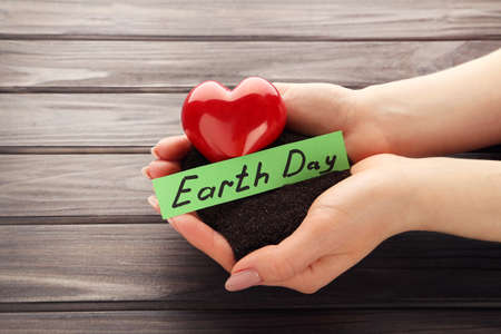 Female hands with soil, red heart and text Earth Day on wooden background