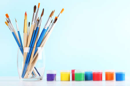 Artistic brushes in glass and colorful gouache paints on blue background