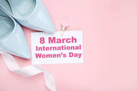 Card with text 8 March International Womens Day, white ribbon and pair of blue high-heeled shoes on pink background