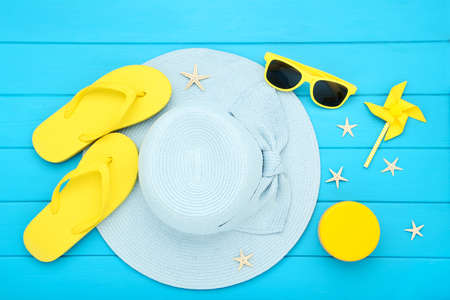 Summer straw hat with sunglasses, flip flops, windmill and starfishes on blue wooden table