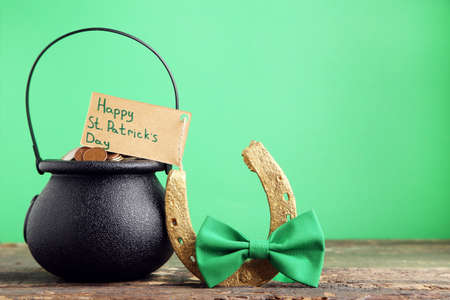 Pot of coins and card with text Happy St. Patricks Day, golden horseshoe and bow tie on green background
