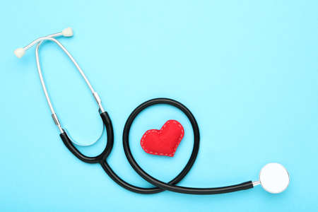 Text Happy Doctor's Day with stethoscope and red fabric heart on blue background