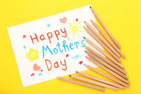 Text Happy Mother's Day with colorful pencils on yellow background Standard-Bild - 167121294
