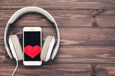 Headphones, smartphone and red heart on wooden background Standard-Bild