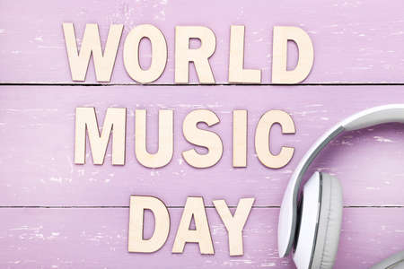 Headphones and inscription World Music Day on purple wooden background Standard-Bild