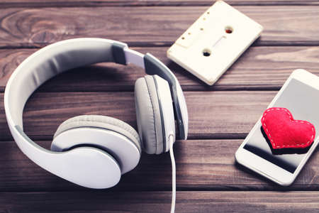 Headphones with smartphone, cassette tape and red heart on wooden background Standard-Bild