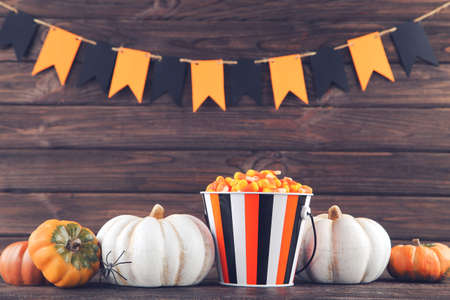 Halloween pumpkins with candies in bucket and paper flags on wooden background Standard-Bild