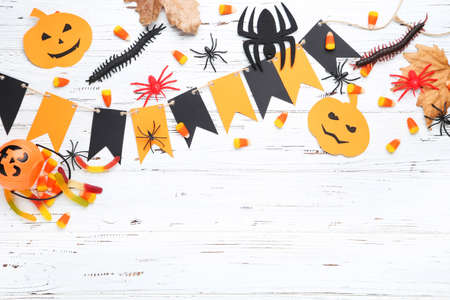 Halloween paper pumpkins, candies, spiders and paper flags on wooden background