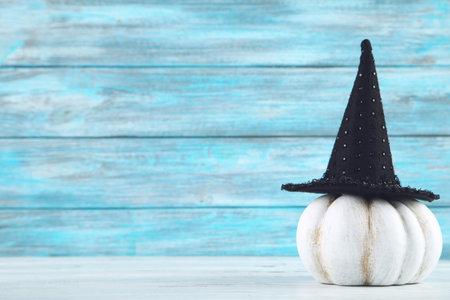 Halloween pumpkin with black hat on wooden background