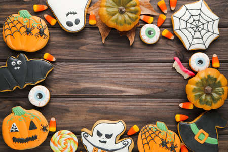 Halloween gingerbread cookies with candies on wooden table
