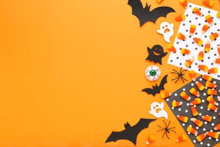Halloween candies with spiders, paper bats, ghosts and eye on orange background Standard-Bild