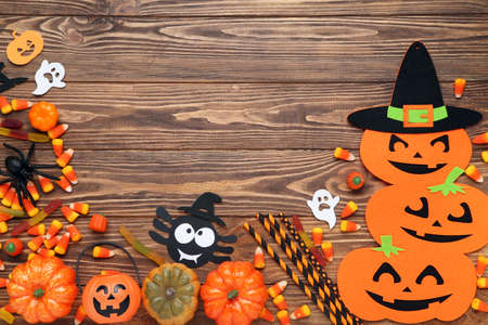 Halloween pumpkins, candies, spider, ghosts and straws on brown wooden table