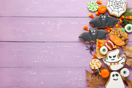 Halloween gingerbread cookies with candies, spiders and dry leafs on purple wooden table