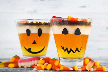 Halloween jelly in glasses with candies on wooden table