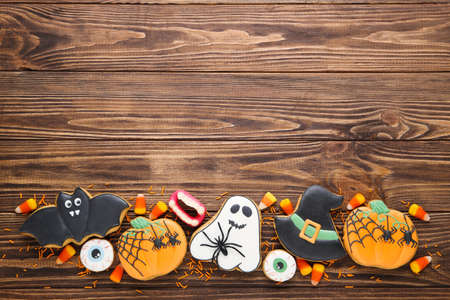 Halloween gingerbread cookies with candies on brown wooden table