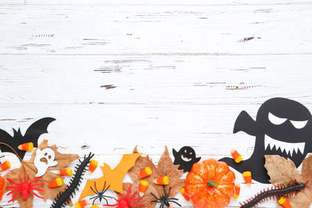Halloween pumpkin, paper ghosts, bats with candies and maple leafs on wooden background