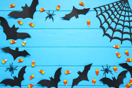 Halloween paper bats, spiderweb with candies and spiders on blue wooden background