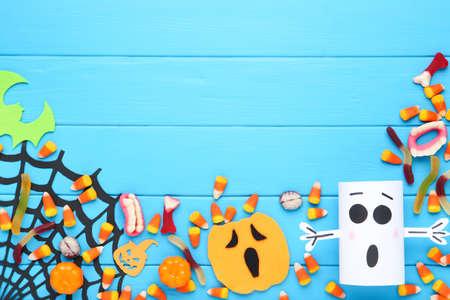 Halloween candies, gelatin with paper pumpkin, ghost and spiderweb on blue wooden background