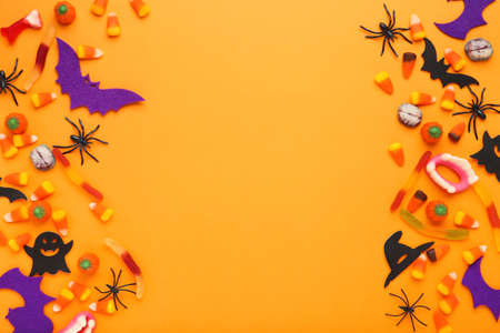 Halloween candies with spiders, paper bats and ghosts on orange background