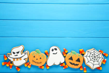 Halloween gingerbread cookies with candies on blue wooden table Standard-Bild