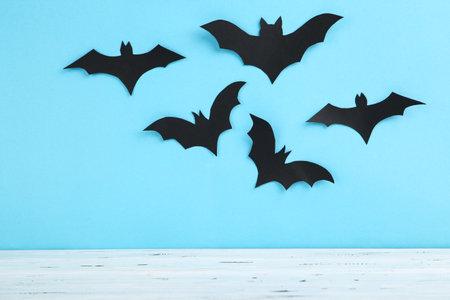 Halloween paper bats on blue background