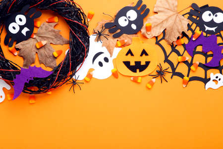 Halloween pumpkins, ghosts, candies, maple leaf and wreath on orange background