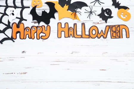 Text Happy Halloween with spiders and paper ghosts, bats, pumpkins on white wooden background Standard-Bild