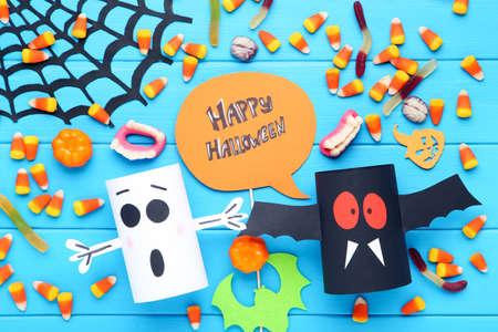 Text Happy Halloween with candies, paper ghosts, pumpkin and spiderweb on blue wooden background Standard-Bild