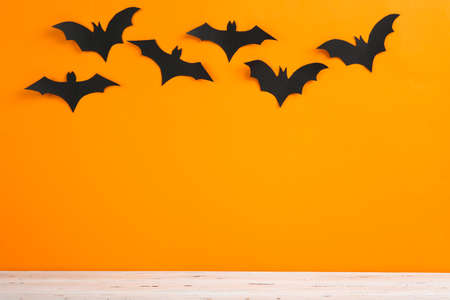 Halloween paper bats on orange background
