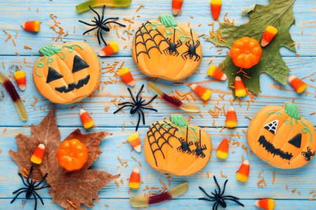Halloween gingerbread cookies with candies, spiders and dry leafs on blue wooden table