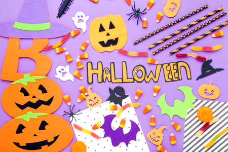 Word Halloween with candies, paper pumpkins, bats, ghosts and spiders on purple background
