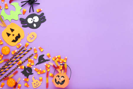 Halloween candies with paper pumpkins, bat, ghosts and spider on purple background
